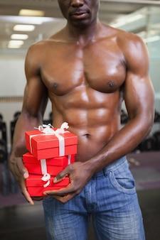 Parte média de um homem musculoso com caixas de presente