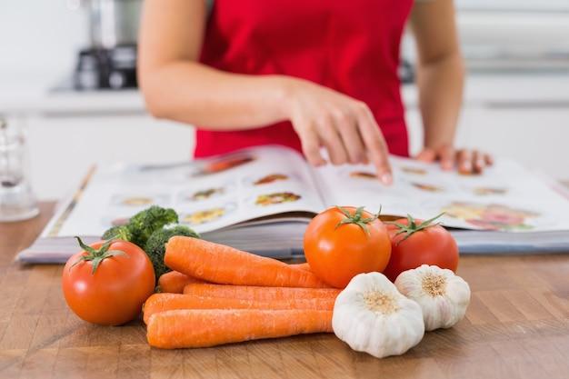 Parte média de uma mulher com livro de receitas e vegetais na cozinha