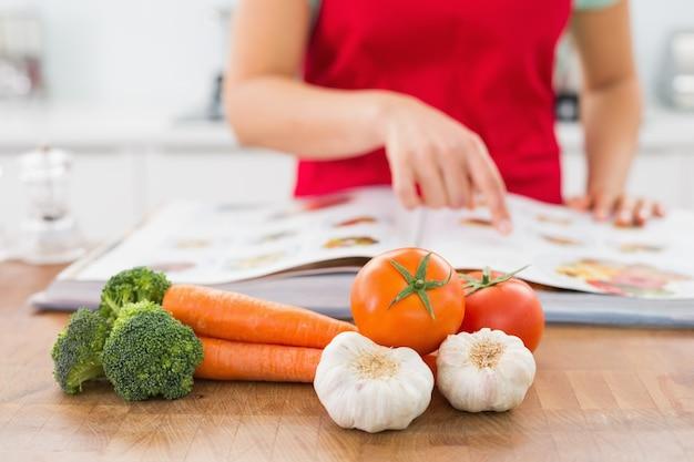 Parte média de uma mulher com livro de receitas e vegetais