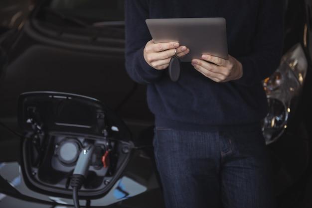 Parte média do homem usando tablet digital enquanto carrega o carro elétrico
