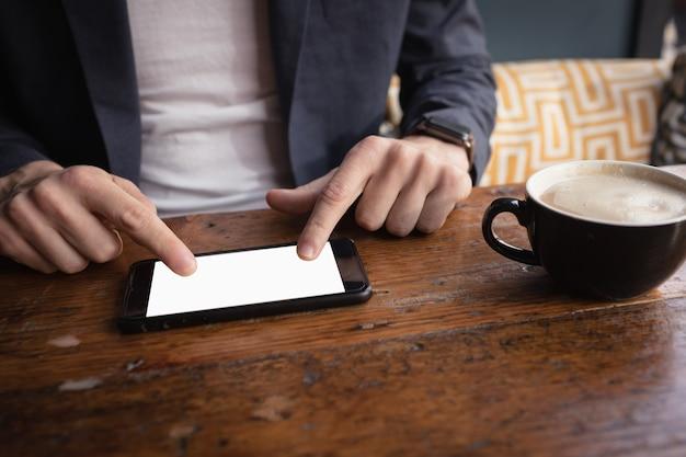 Parte média do homem usando tablet digital enquanto toma café