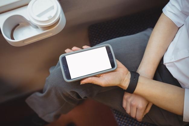 Parte mediana de mulher segurando um telefone celular