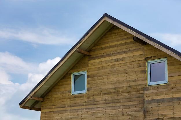 Parte superior da casa nova do detalhe do close-up de pranchas e placas de madeira com as duas janelas plásticas estreitas do sótão.