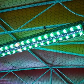 Parte superior do parque de diversões à noite com luzes verdes e azuis