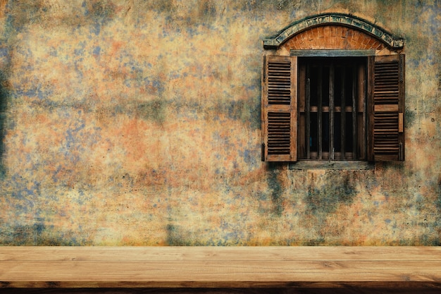 Parte superior vazia da cadeira de madeira com parede de cimento velha e um fundo de janela de madeira.