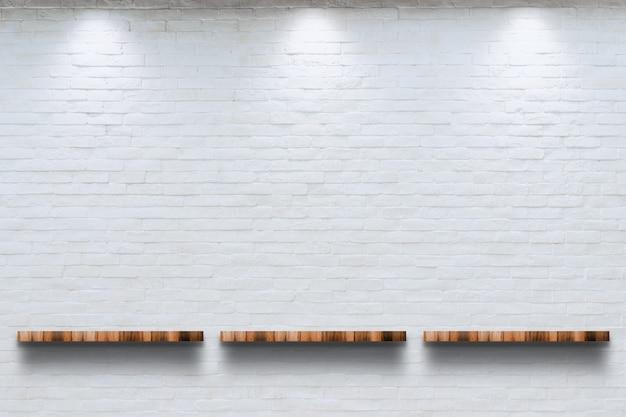 Parte superior vazia da prateleira de madeira com fundo branco da parede de tijolo.