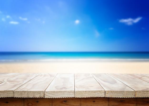 Parte superior vazia da tabela ou contador de madeira e vista da praia tropical. para a exposição do produto