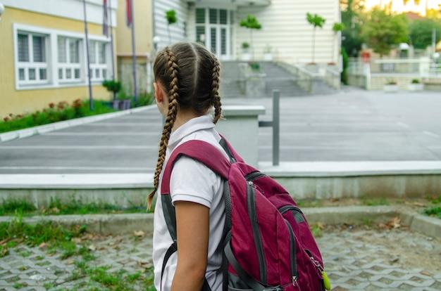 Parte traseira da criança da menina que vai à escola com a trouxa vermelha.