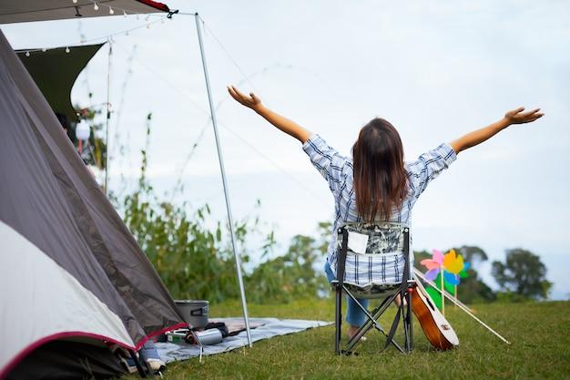 Parte traseira da mulher asiática sentada na cadeira de piquenique e curtindo com a beleza natural ao acampar com a família no local de acampamento.