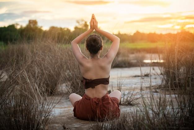 Parte traseira da mulher da ioga do por do sol no fundo da natureza do campo fora