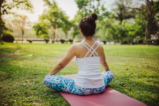 Parte traseira da mulher sentada e meditando
