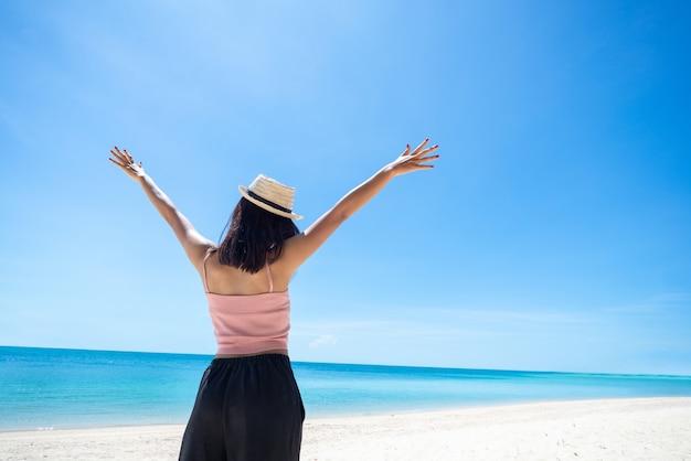 Parte traseira da pele bronzeada mulher vestindo blusa rosa e chapéu de palha com os braços em pé estendidos no céu. olhando para o mar e o céu fresco. viagens de verão. relaxe, férias e tropical, conceito confortável.