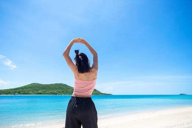 Parte traseira da pele bronzeada mulher vestindo blusa rosa e chapéu de palha com os braços em pé estendidos no céu. olhando para o mar e o céu fresco.