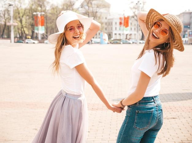 Parte traseira de duas meninas de hipster loira sorridente jovem bonita em roupas da camiseta branca na moda verão e chapéu. . par, segurando, um ao outro, mãos