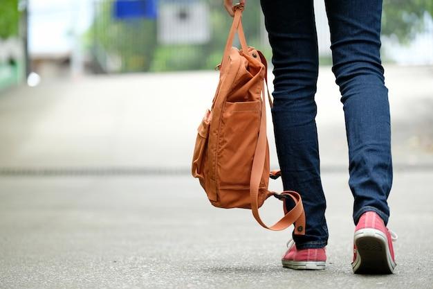Parte traseira, de, menina estudante, segurando, bolsa escola, enquanto, andar, em, escola, campus, fundo