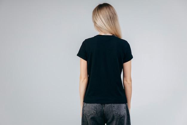 Parte traseira de menina loira elegante vestindo camiseta preta posando