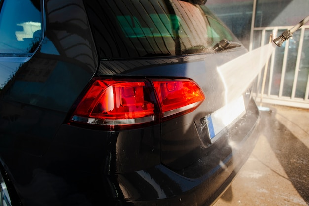 Parte traseira de um carro preto limpo com água