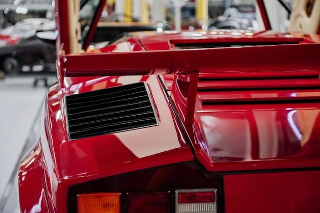 Parte traseira de um carro vermelho luxuoso e moderno estacionado dentro de uma exposição