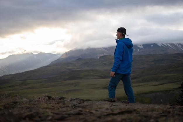 Parte traseira de um homem alto, caucasiano, vestindo jaqueta em pé sobre a montanha de neve na pista de laugavegur, islândia. promover um estilo de vida saudável.