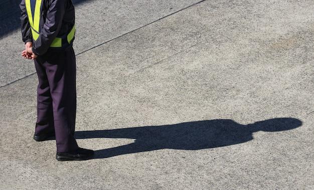 Parte traseira de um trabalhador de controle de canteiro de obras em pé no chão da pista do aeroporto.