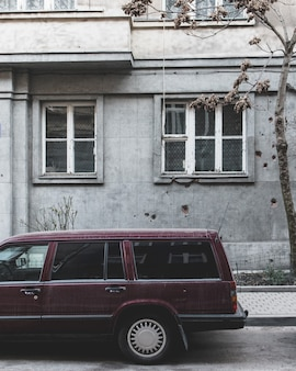 Parte traseira de um velho carro familiar com um prédio cinza