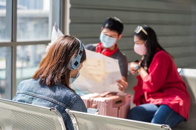 Parte traseira de uma jovem com máscara facial ouvir streaming de música online e reproduzir mídia social no assento de espera do terminal do aeroporto.