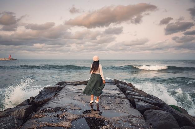 Parte traseira de uma jovem mulher asiática em pé e posando no cais rochoso e ondas batendo na praia de jumunjin em gangneung, coreia do sul