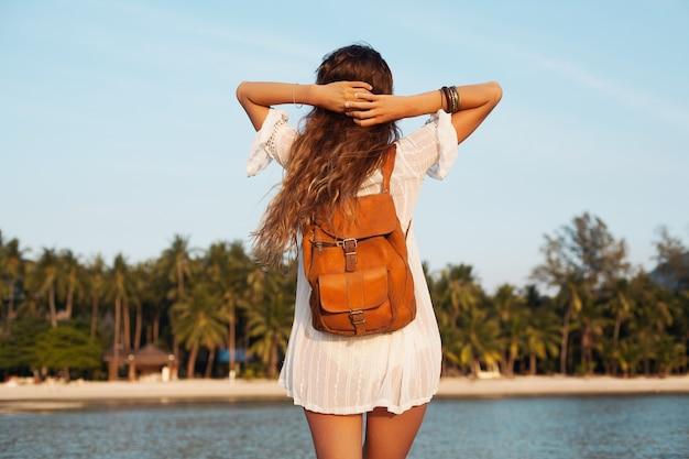 Parte traseira de uma linda mulher vestida de branco andando despreocupada na praia tropical com mochila de couro.