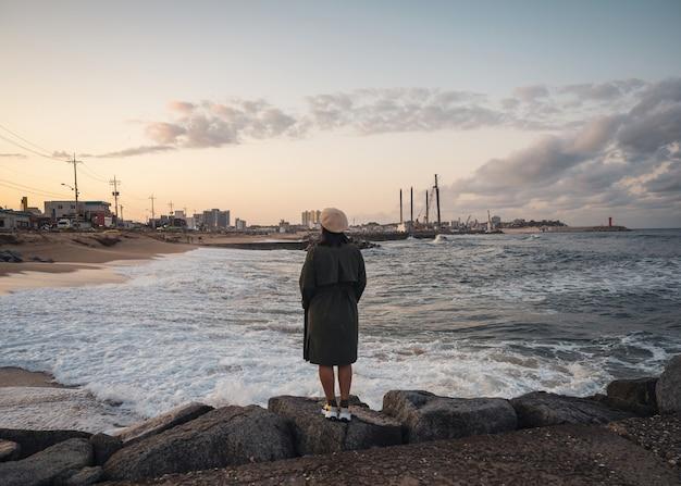Parte traseira de uma mulher com casaco de inverno e chapéu em pé no cais rochoso com ondas batendo no pôr do sol na praia de jumunjin