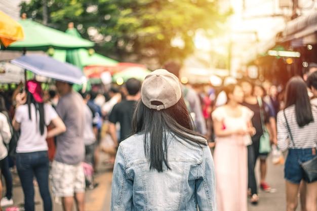 Parte traseira do cabelo preto de mulheres com jaqueta jeans e chapéu no borrão multidão anônima