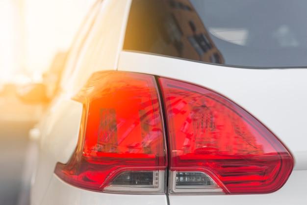 Parte traseira do carro branco com luz traseira vermelha