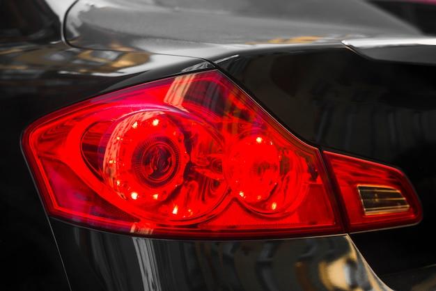 Parte traseira do carro escuro com luz traseira vermelha