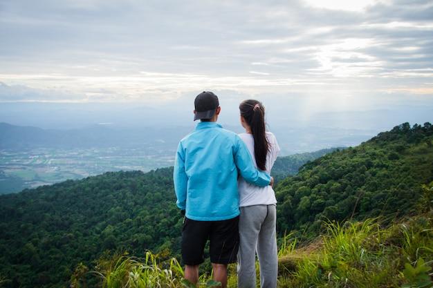 Parte traseira do casal amor sentir mulher feliz ficar top mountain olhando vista com névoa e nuvem