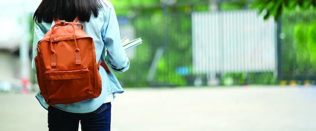 Parte traseira do estudante universitário com mochila ao ir para a faculdade, andando na rua, adolescente no campus, conceito de educação