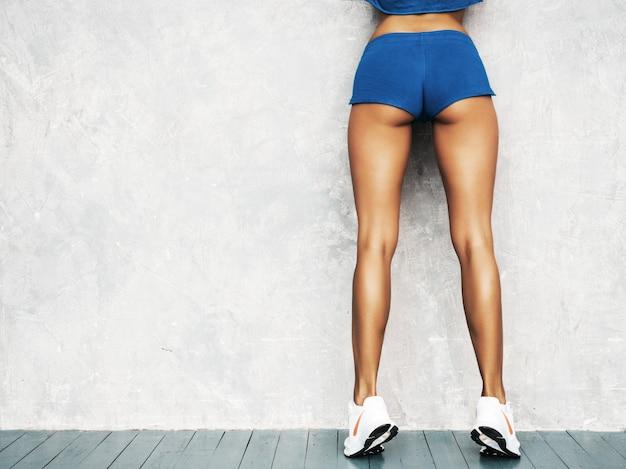 Parte traseira do fitness mulher em roupas esportivas, olhar confiante. jovem fêmea vestindo roupas esportivas. bela modelo com corpo bronzeado perfeito. feminino posando no estúdio perto da parede cinza