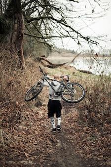 Parte traseira do homem carregando bicicleta nas costas andando perto do lago