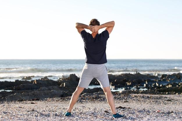 Parte traseira do homem de esportes olhando no mar