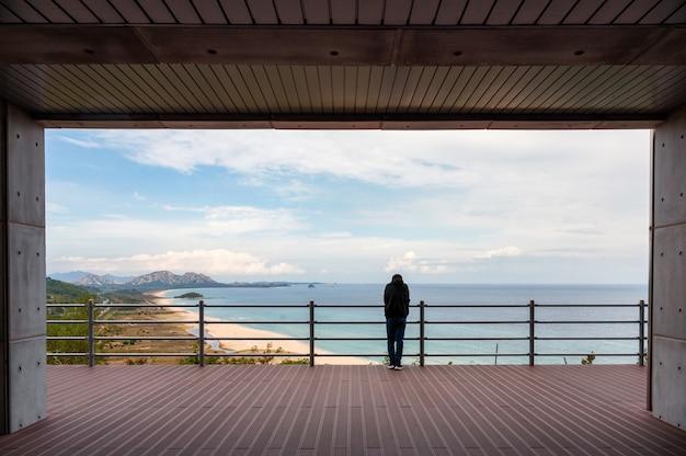 Parte traseira do homem em pé e olhando para a vista do mar da fronteira na varanda de madeira