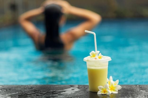 Parte traseira do mulher na piscina com shake de frutas.