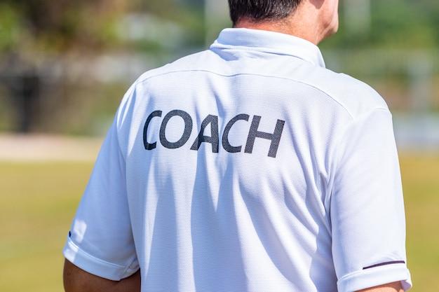 Parte traseira do treinador de desporto masculino vestindo camisa de treinador em um campo de esporte ao ar livre