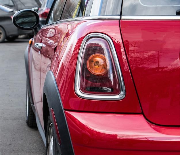 Parte traseira e lateral de um mini cooper vermelho um farol traseiro de um mini cooper vermelho estacionado na rua