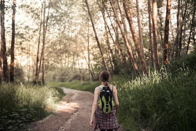 Parte traseira vie de mulher andando na estrada de terra na floresta