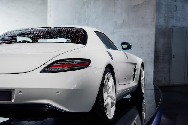 Parte traseira, vista lateral de um carro esporte branco legal com luz de fundo de diodo direito, espelho azul com pisca-pisca, porta-malas, rodas de liga leve e pneus de baixo perfil, reflexo das luzes na janela perto da parede cinza.