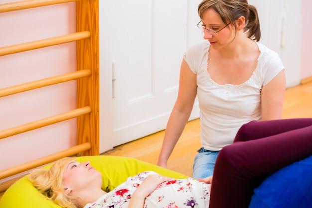 Parteira dando assistência pré-natal para mãe grávida