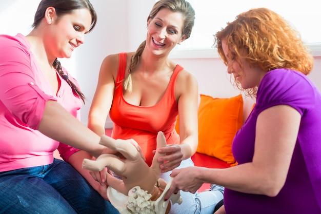 Parteira explicando o processo de nascimento para mulheres grávidas durante a aula pré-natal
