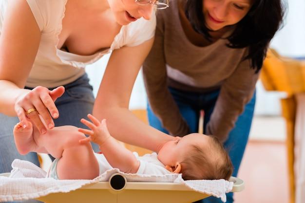 Parteira medindo peso ou recém-nascido