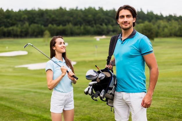 Parteners de golfe carregando saco de golfe