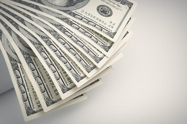 Partes das notas de cem dólares estão localizadas à esquerda com um ventilador.
