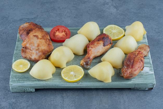 Partes de frango grelhado e batatas cozidas na placa de madeira.