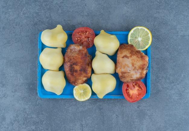 Partes de frango grelhado e batatas cozidas no quadro azul.